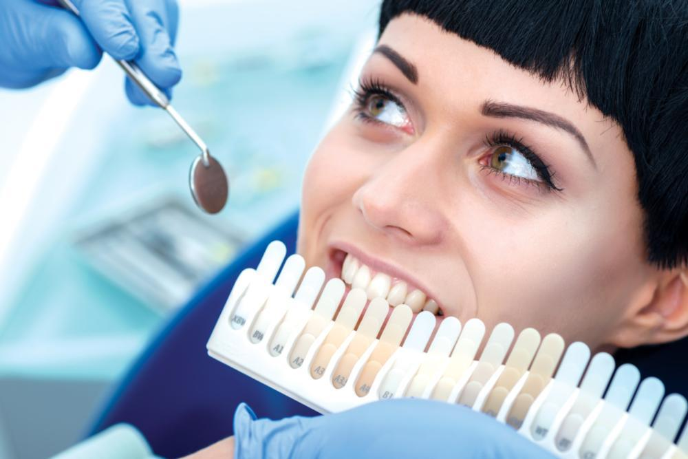 Woman Comparing Whiteness of Teeth to Shade Scale | Teeth Whitening in Gaithersburg