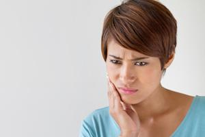 A woman holds her hand up to her jaw | Root Canals Gaithersburg MD