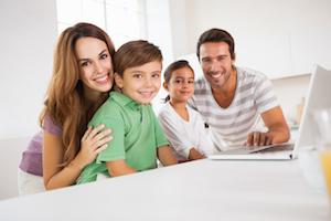 A family smiles together at a desk | Top Dentist Gaithersburg